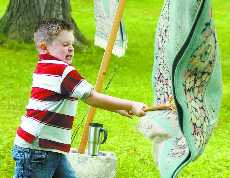 homesteaddaysJH1 - Nick DePorter gives a might swing with a broom to a rug as the Gorham elementary School second grader got a chance to see what it was like back in the 19th Century on Wednesday June 6 at the Granger Homestead.