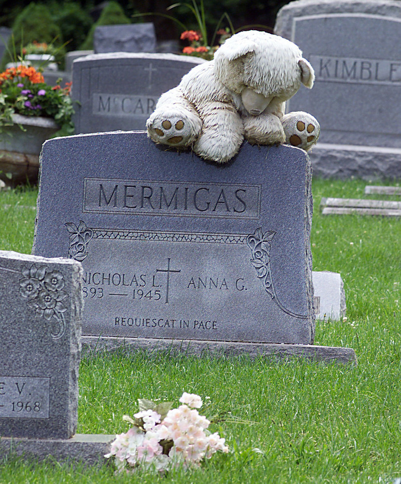 A wet and weatherd teddy bear sits atop a tombstone in Calvary Cementary. Recently vandal's toppled over nearly two dozen stones.