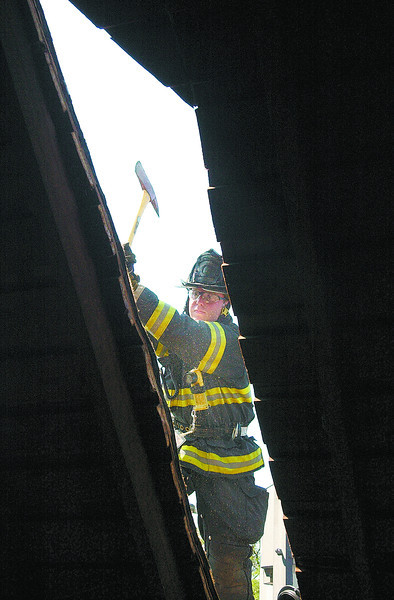 firedrillJH5 - George Smith of the Canandaigua Fire Department swings an ax on top of a three-story home on Atwood Street on Thursday as firefighters practiced ventalation techniques, the second day they drilled at this old home.