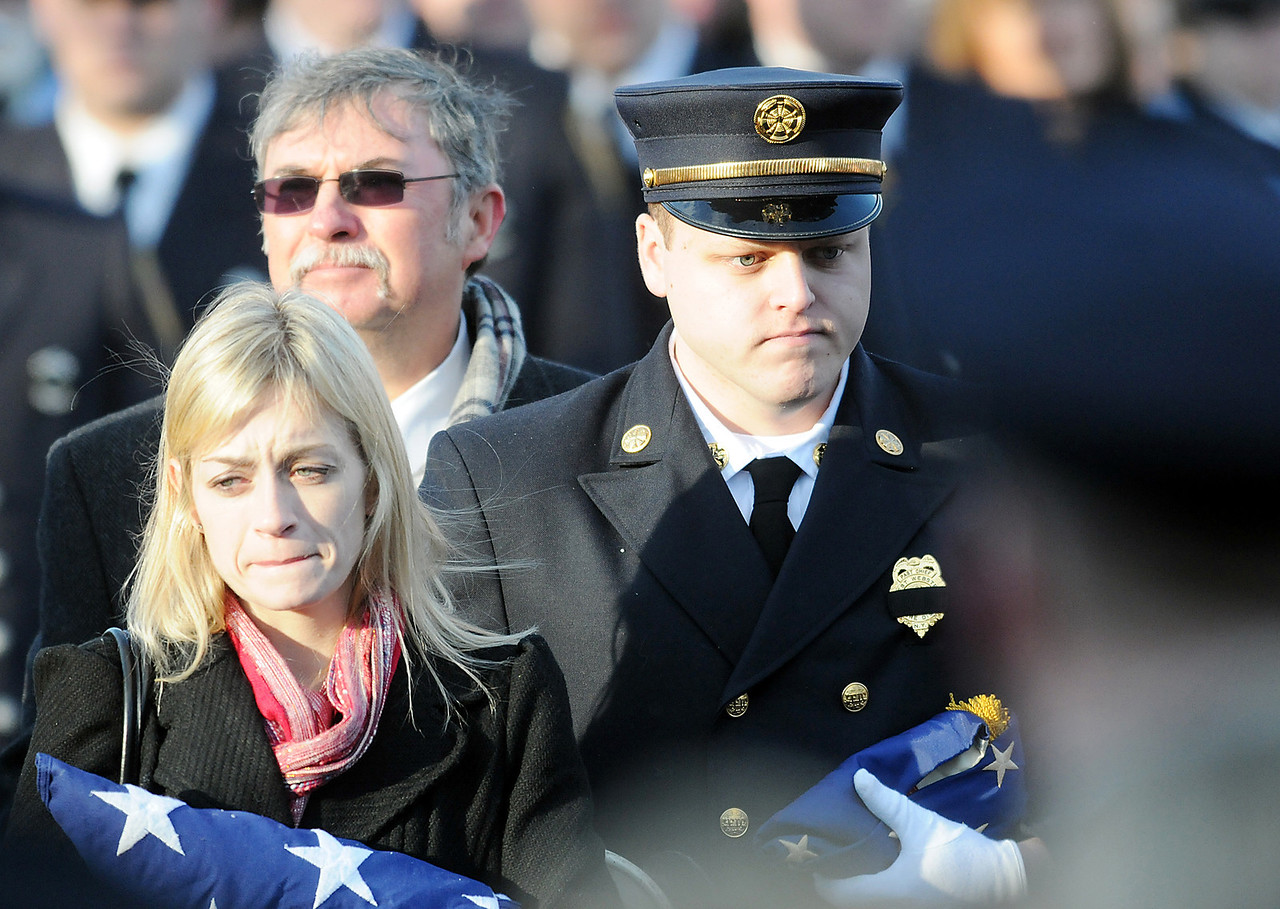 Jack Haley/Messenger Post<br /> Kimberly Chiapperini (left) holds an American Flag during a funeral service for her husband Lt. Mike Chiaperini as does their son Nicholas Chiapperini on Sunday. Chiapperini, a volunteer firefighter, was fatally shot after he arrived at a house fire set by an ex-convict who later killed himself.
