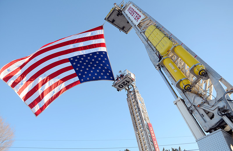 Jack Haley/Messenger Post<br /> Two aerial trucks begin lower the giant American Flag that it held high above Ridge Road for the cermony for Lt. Mike Chiaperini.