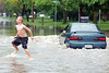 jhflood1 - Jordan Quayle, 11 of Mohawk Ave, jumps the waves created by a passing car going through flood waters on Canandaigua Ave on Friday.