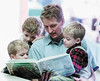 "jhread1 - Kent Gilges of Canandaigua reads Bimwili and the Zimwi to his three sons Oliver (left) 3, Alexander, 5, and Nicholas (right) 3, during the ""Read Around the World"" program sponsored by the Family Reading Partnership."
