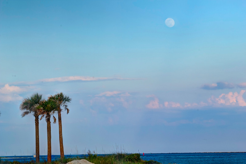 The moon pops out of the clouds just as the Carnival Fascination disappears over the horizon as seen from Huguenot Park.
