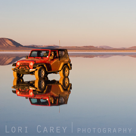 Red Jeep Wrangler reflected in the water of a dry lake in the Mojave desert. A winter storm brought an unusual amount of snow to the desert, creating a reflection pool in what is normally a dry lake bed.