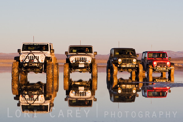 Four Jeep Wranglers reflected in the water of a dry lake in the Mojave desert. A winter storm brought an unusual amount of snow to the desert, creating a reflection pool in what is normally a dry lake bed.