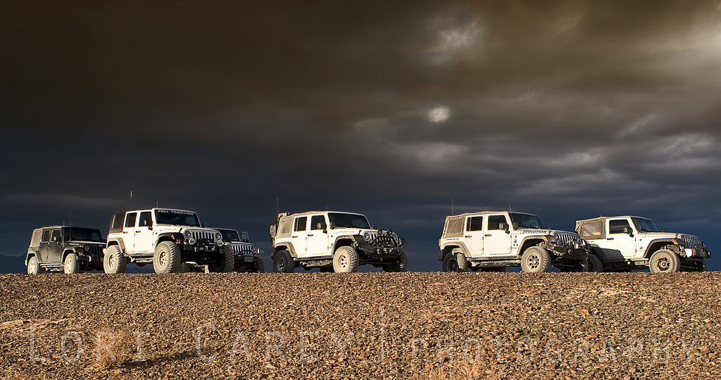 Jeeps on desert trail under a stormy sky