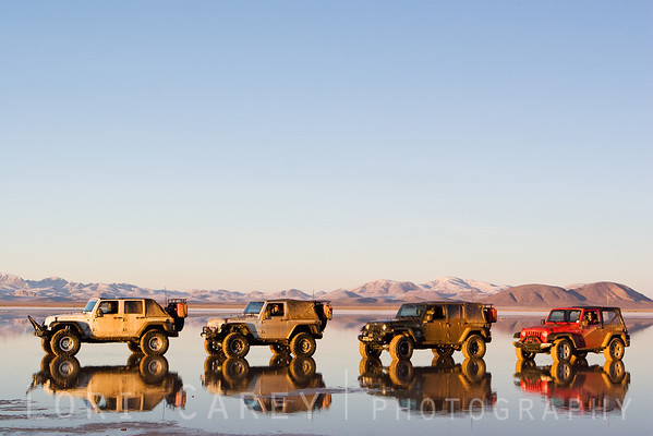 Four Jeep Wranglers reflected in the water of a dry lake in the Mojave desert. A winter storm brought an unusual amount of snow to the desert, creating a reflecting pool in what is usually a dry lake bed.