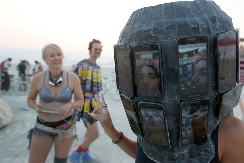 A participant tries on a wearable piece of art during the annual Burning Man arts and music festival in Black Rock Desert, Nev. on Aug. 31, 2017.