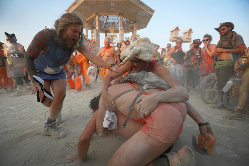 Participants wrestle in front of the Man during the annual Burning Man arts and music festival in the Black Rock Desert of Nevada on Aug. 31, 2017.