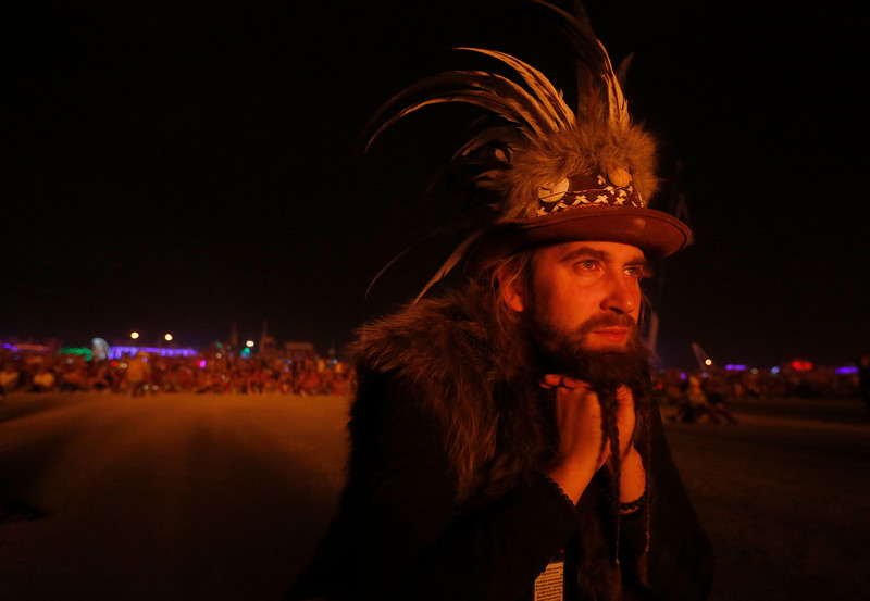 A participant watches the annual burning of the Man during the annual Burning Man arts and music festival in the Black Rock Desert of Nevada on Sept. 2, 2017.