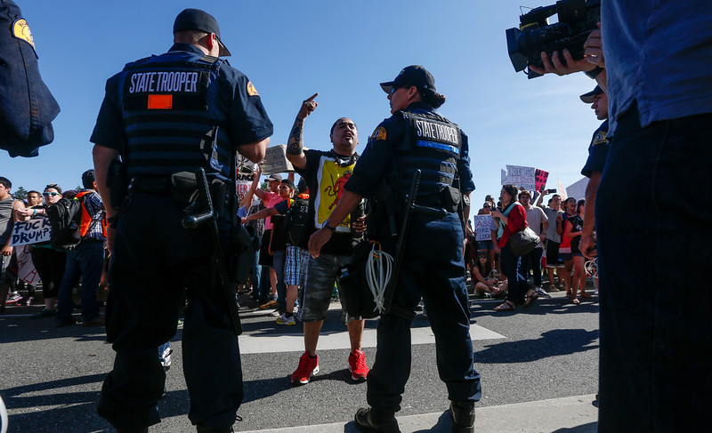 A protester stands in front of Washington state troopers at a rally outside a campaign stop for Republican presidential nominee Donald Trump in Lynden, WA on May 7, 2016.