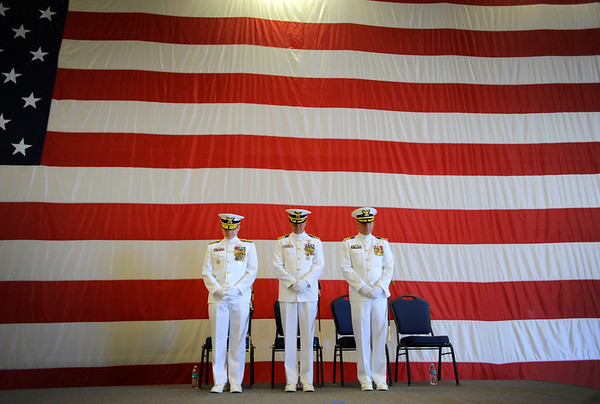 Coast Guard Rear Adm. David Throop, left, commander of the 13th Coast Guard District, Capt. Michael Trimpert, middle, and Capt. Michael Mullen bow their heads during the benediction at the Changing of the Command ceremony held at the Coast Guard station in North Bend on Friday. Coast Guard Capt. Michael Mullen assumes command of Sector North Bend from Capt. Michael Trimpert.  Rear Adm. David Throop, commander of the 13th Coast Guard District, presided over the ceremony.
