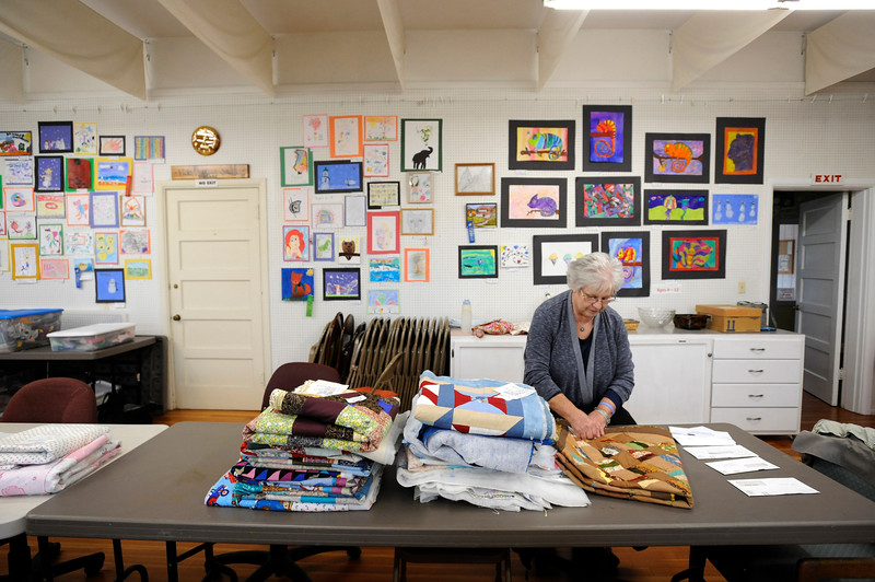 Mary Graham, a member of the Coquille Valley Art Association, organizes partially complete quilts in preparation for the Quiltathon event on March 4th, 2017. The finished quilts are donated to the CASA Program of Coos County.
