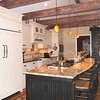 Wood's Kitchen<br /> <br /> The galley configuration with a large island allowed a convenient traffic flow for buffet style gatherings while also providing entertainment seating for more intimate gatherings.<br /> We Raised the flat ceiling to vault and added distressed beams.