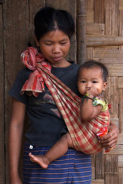 LUANG PRABANG AREA. BORHIA (SAY: BOHE) VILLAGE. KHAMU MOTHER WITH BABY. LAOS.