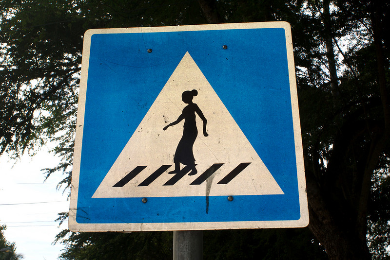 LUANG PRABANG. STREET SIGN OF LAO LADY CROSSING THE STREET. LAOS.