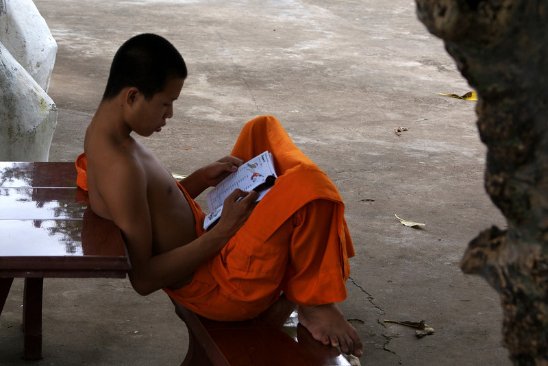LUANG PRABANG. YOUNG MONK IS STUDYING ENGLISH. LAOS.