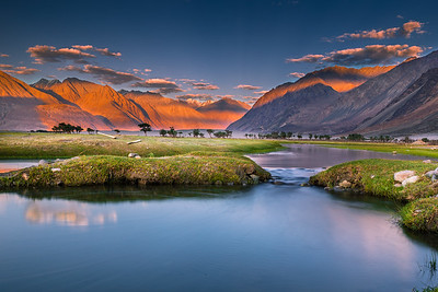 Himalayan desert - Sand dunes, towering  mountain ranges illuminated by warm rays of the sun before sunset, and shyok river