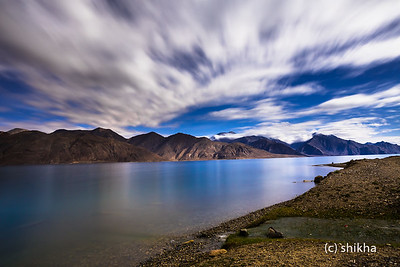 It was near full moon. Was cloudy, windy and was shivering cold. Took this shot as soon as the moon showed itself out of the clouds. You can see some star trails though clouds hid most of them. That night it rained like monsoon at Pangong lake !! Locals told, it was very very unusual to see that kind of rain. The mountains were seen dusted with snow next day when the clouds cleared off