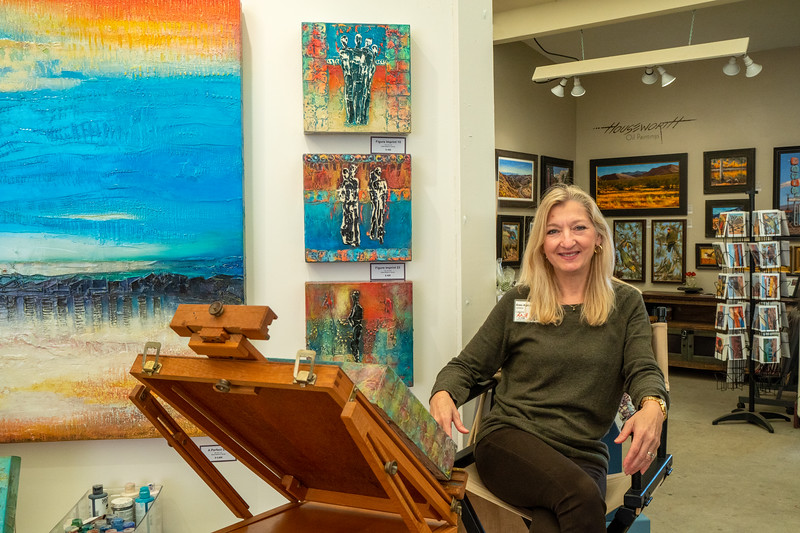 At her easel, Eren Alptekin showcasing her colorful mixed-media paintings