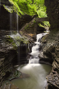 A man made bridge passes behind Rainbow Falls before crossing over the gorge in Watkins Glen State Park, New York.
