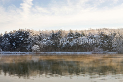 Morning sunlight highlights a golden mist on Lake Shenandoah on a cold and snowy morning.