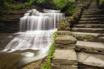 Stone stairs rise next to an unnamed waterfall in Buttermilk Falls State Park, New York.