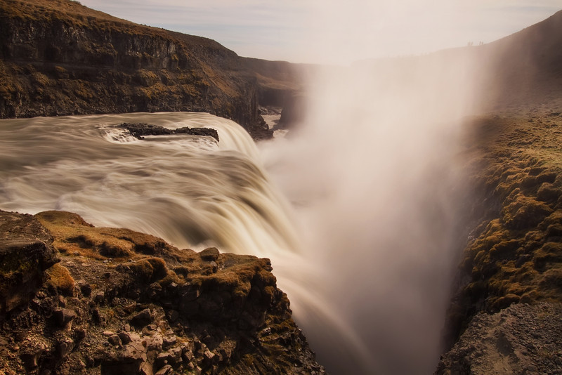 <H3>One Step Closer... </H3> I would not recommend getting any closer to this massive waterfall than this! Two things about this image indicate the sheer scale and power of Gullfoss (Golden Falls)  - the size of the mist column at any given time and the tiny humans adoring the view from the cliff to the right. Iceland has countless spectacular waterfalls often with the most notable ones having a distinct unmistakable look. Gullfoss seems to be one of the biggest in the country and also attracts the largest crowds due to its close proximity with Reykjavik...kinda like Niagara falls is to Toronto.