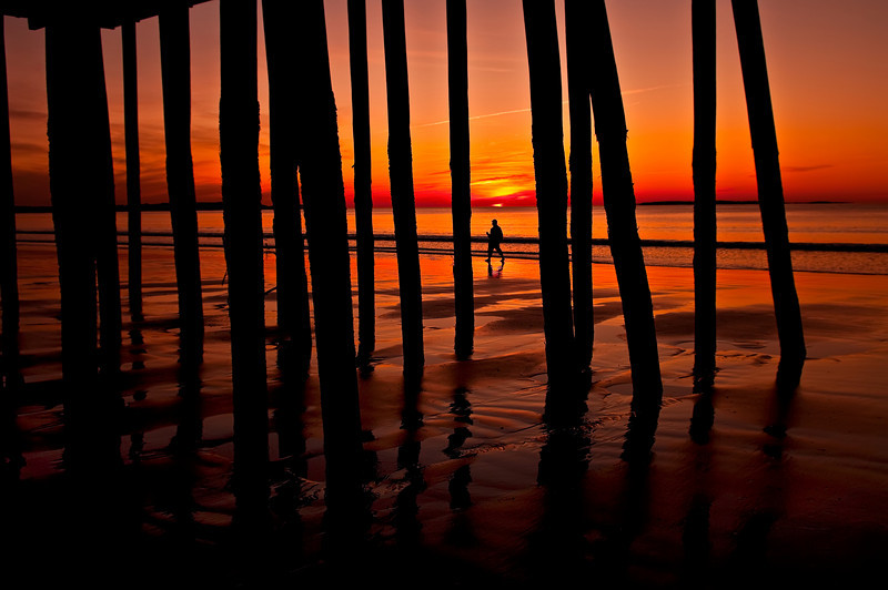 The Human Element<br /> A lone figure walks among the pilings of the Old Orchard Beach pier during a glorious sunrise.