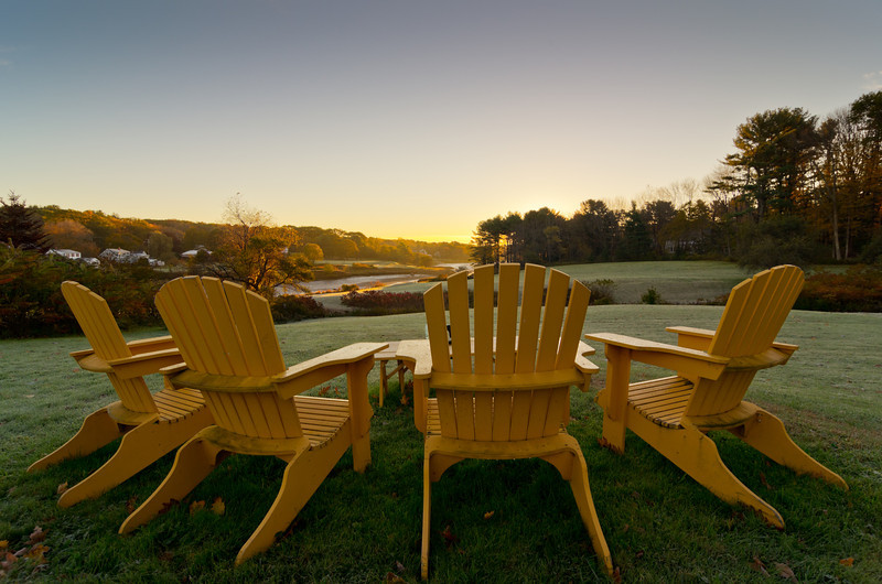 Adirondack chairs overlook a beautiful misty sunrise on the River Road in York, Maine.
