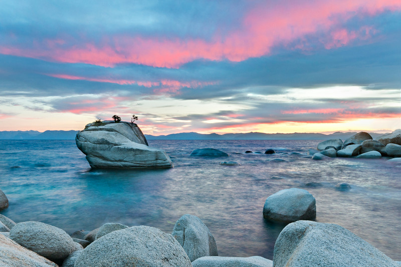 """""""Sunset on the Bonsai Rock and Tree in Lake Tahoe"""" The massive rocks and boulders in Lake Tahoe almost look like stepping stones out to the Bonsai tree at sunset here in Lake Tahoe.  This is another summer shot of the Bonsai Rock and Tree along the eastern shore in Lake Tahoe.  It didn't seem like there was going to be any sunset that night.  At the last minute the sky just lit up with a pink glow!"""