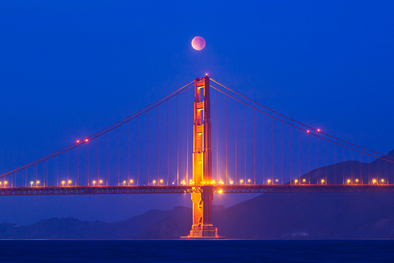 """""""Lunar Eclipse over the Golden Gate""""  I went out at sunrise this morning not sure what to expect!  What an awesome sight!  The Lunar Eclipse continued to change.  The blue skies at sunrise with the red moon overhead were just a sight to watch!  It disappeared into the fog just minutes after I shot this! It was worth the 3am start to our fun shooting!  My image made the cover of MSNBC's web site!     Thanks for viewing my images!  You can see more on my website here or follow me on my Facebook page here:  <a href=""""http://www.facebook.com/pages/Yosemite-and-Bay-Area-Nature-Photography-by-John-Harrison/190152125697"""">http://www.facebook.com/pages/Yosemite-and-Bay-Area-Nature-Photography-by-John-Harrison/190152125697</a>"""