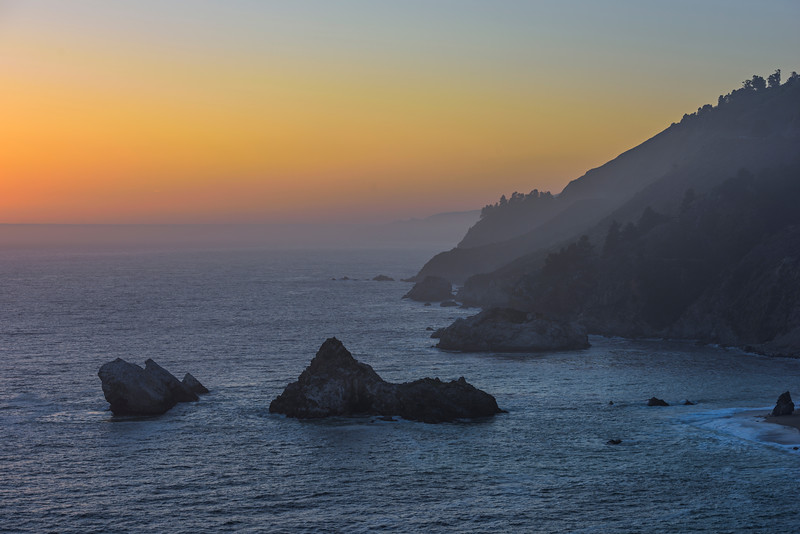 """Sunset Along the Northern California Coastline""  Sharing an image from our trip down to Big Sur this past weekend with the family. The sun had already set and the outlines of the cliffs and hills can be seen with a little haze from the fog.  Love the simple colors and rocks down in the water.  The depth of the hills along the Northern California Coastline can be seen as it goes off into the distance."