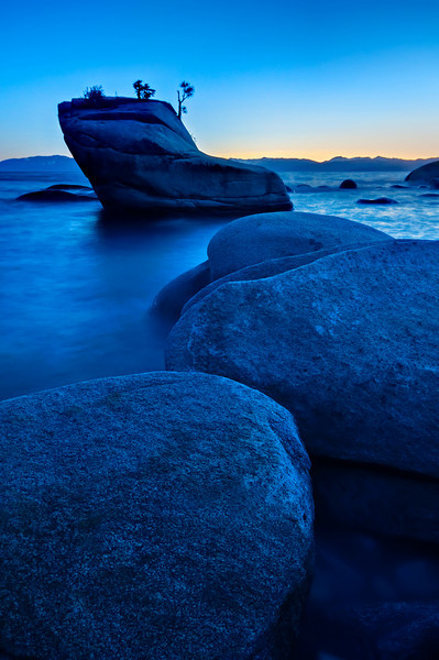 """Lake Tahoe Bonsai Tree at Sunset""  The massive rocks and boulders in Lake Tahoe almost look like stepping stones out to the Bonsai tree at sunset here in Lake Tahoe.  My first trip to the elusive tree and large waves were on the lake.  I used a long exposure at dusk to smooth the water out.  The vibrant sunset on the horizon filled the sky."