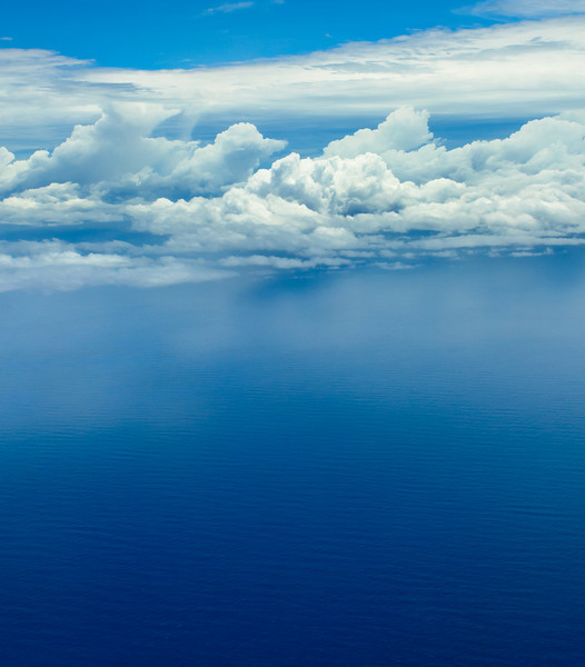 """Clouds over the Blue Ocean"" I thought I would see what folks thought of this and the other blue only image! I shot this from the airplane coming into the Big Island in Hawaii and just love the blue tones of the ocean below with nice definition of clouds (remember, I like clouds!) The other image is quite minimalist and might be considered TOO artsy! Let me know what you think!"
