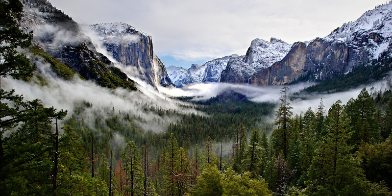 """Tunnel View Panorama at Sunrise in Winter"" Yosemite National Park.  I never get tired of heading up to Tunnel View in Yosemite.  Grand views of El Capitan and Bridalveil Falls with Half Dome Tucked in behind.   Every time I go it is totally different! This morning the low fog and clouds kept shifting around.   One minute the fog would totally obscure our view and the next minute it was totally clear!  The timelapse of this looks amazing!   This is a 1:2 ratio shot that will look good as a 20"" x 40"" (minimum!) panorama on your wall!"