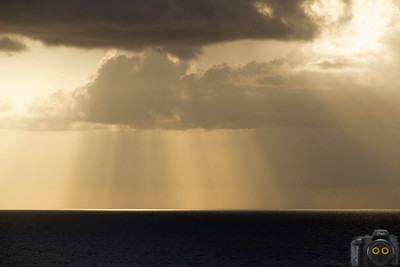 Clouds over the Alantic Ocean with sunbeams streaming down.