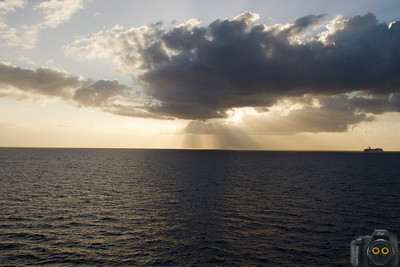 Clouds over the Alantic Ocean with sunbeams streaming down near a cruise ship..