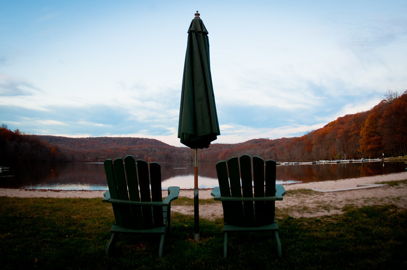 Two green lawn chairs placed on each side of a green outdoor umbrella sitting on grass on the edge of a river with mountains and a blue sky in the background by Alex Kaplan, photographer http://www.alexkaplanphoto.com