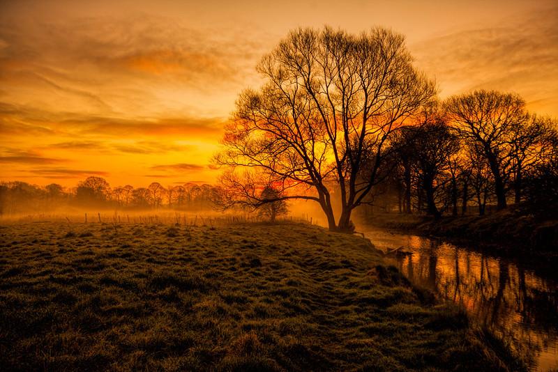 Early morning mist over the River Darwen flowing through Witton Park, Blackburn, Lancashire.