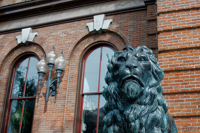 Statue of a lion guarding a brick building