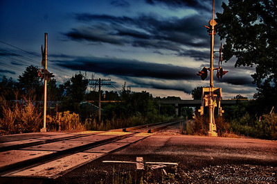 Warmly-lit railroad crossing at night