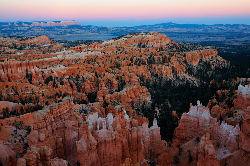 A vivid twilight wedge forms over the eastern horizon at dusk as hoodoo formations take on a warm glow in the main amphitheater, Bryce Canyon National Park, Utah, USA.
