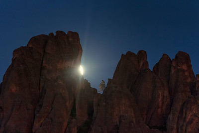 A full moon rises through high peaks at Pinnacles National Monument, California, USA.