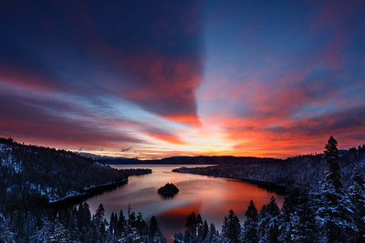 Dawn light casts a warm glow following an overnight snow storm at Emerald Bay, Lake Tahoe, California, USA.