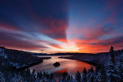 Dawn light casts a warm glow following an overnight snow storm at Emerald Bay, Lake Tahoe, California, USA.