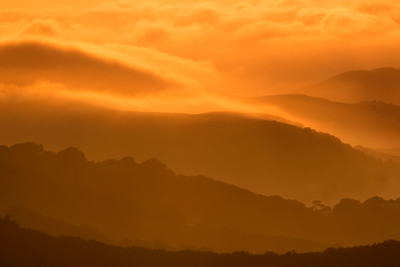 Evening fog slips through the valleys of the Gabilan Mountains high above Monterey Bay, California, USA.