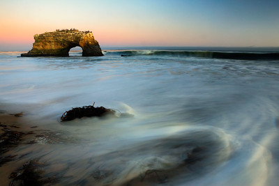 An arch stands against a twilight sky at Natural Bridges State Park, Santa Cruz, California, USA.