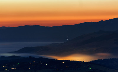 Summer fog rools over Monterey Bay and is illuminated from the lights of small towns underneath. A warm glow holds along the horizon an hour past sunset. Image captured from Fremont Peak State Park looking towards Santa Cruz, California, USA